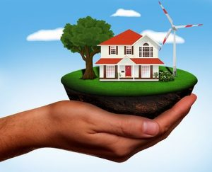 Hand holding an energy efficient home with a wind turbine in the garden