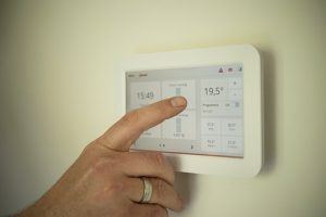 Finger pointing to a smart energy meter on the interior wall of a property